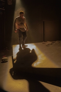 A man is walking on a stage with light behind him