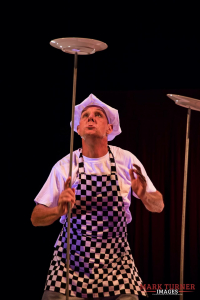 A middle aged man wearing a black and white checked apron, balancing plates on sticks